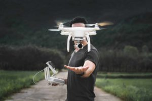 Pricing your used and second hand drones, man controlling small white drone, holding controller.