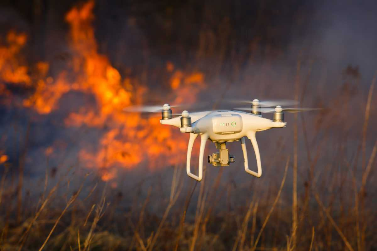 Image of Small white drone flying near fire in a field.